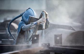 Man sandblasting metal parts